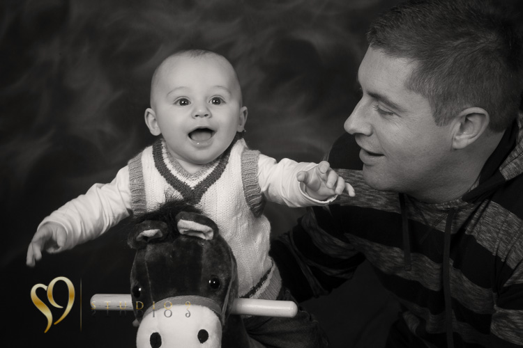 Dad helps his son on the rocking horse. Photography by Studio9.